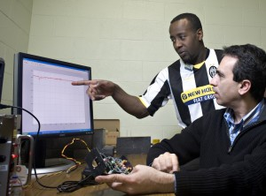Abi Farsoni, right, and his graduate student, Abdulsalam Alhawsawi, discuss gamma and beta radiation waves visible on a computer screen. On the desk is the detector developed by Farsoni and colleague David Hamby. (Photo: Karl Maasdam)
