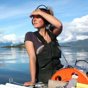 Michelle Fournet scans the Alaskan horizon as she listens to the first whale calls of the 2013 field season from the R/V Noble Steed in front of the Five Finger Lighthouse.