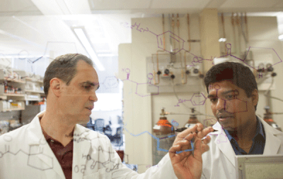 Professor Rich G. Carter (left), co-founder and CEO of Valliscor LLC, confers with Rajinikanth Lingampally, a research associate at Oregon State. (Photo: Chris Becerra)