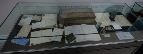 A low glass case with a collection of papers, labels, letters and a wooden box