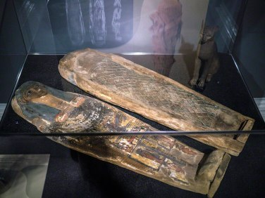 A mummified cat, wrapped and covered in a beaded cover. It lies in a small anthropoid coffin; the lid is sitting beside it