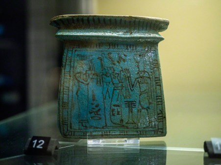 A blue faience pectoral, rectangular in shape, with Osiris and Horus painted on in black outlines