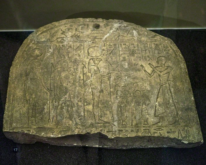 The top portion of a broken stela showing a man wearing a long kilt standing before a table of food offerings and three gods