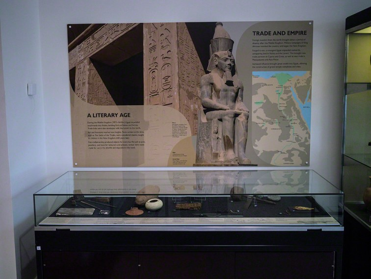 A low glass case containing artefacts, with an information panel on the wall behind. The has a map of Egypt, a royal statue and part of a temple wall with hieroglyphic inscription