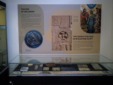 A low, glass display case with artefacts and an information panel on the wall behind containing details about the Hellenistic and Byzantine eras in Egypt