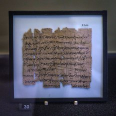 A square piece of papyrus with a little damage around the edges. The text is written in black ink and the papyrus is in a black frame with white backing