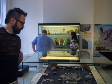 Looking at two display cases containing artefacts - the one in the foreground is a low case and the one in the background a tall one with three selves. There are three people in the room looking at the cases