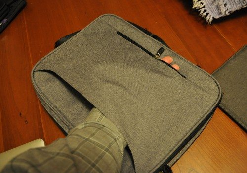 The rear pocket can be zipper open to use with rolling luggage.