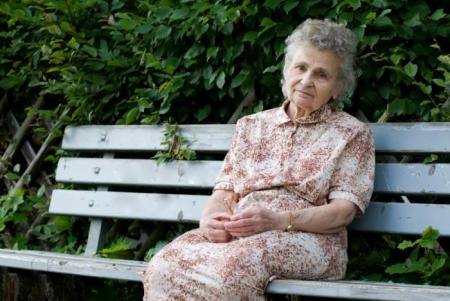 older-woman-on-bench-looking-sad