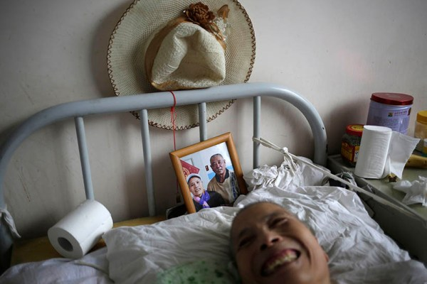 A woman lies in bed with a photo of her husband behind her at Songtang Hospice, Beijing, July 19, 2016. Her husband visits the hospice every day.