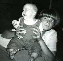 My big sister holding me as a baby.