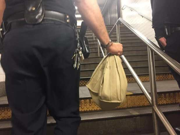 """Seven"" is carried out of the station by a police officer. (DANNY LEWIS/NEW YORK DAILY NEWS)"