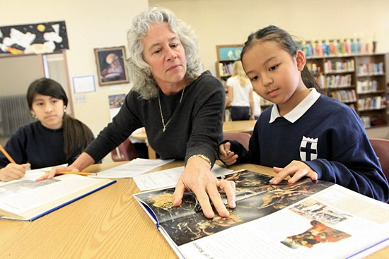 Jane Hileman, center, principal of St. Helena School in Minneapolis, helps fifth-graders Heiry Rocano, left, and Cindy Lor with reading in the school library. Formerly an English teacher, she enjoys the chance to work with students. Dave Hrbacek / The Catholic Spirit