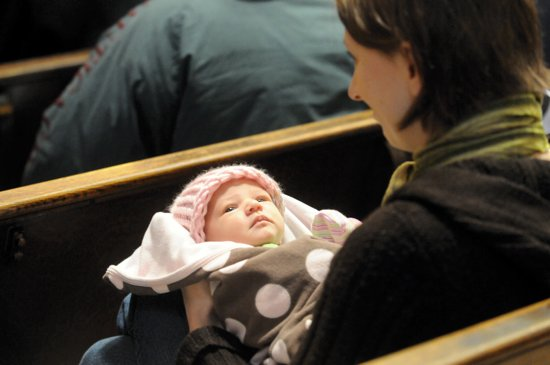 Ali Gardner, a member of the Cathedral of St. Paul, holds her 2-week-old daughter Claire during the prayer service. (Dianne Towalski/The Catholic Spirit)