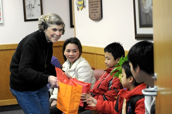 Mary Jo Copeland gives welcome bags to members of a new family at Sharing and Caring Hands in Minneapolis before sending them across the street to their new temporary home at Mary's Place Feb. 11.  Dianne Towalski / The Catholic Spirit