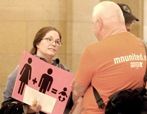 Lizz Paulson talks to a supporter of same-sex marriage while holding a sign protesting the bill to change the definition of marriage. (Dianne Towalski/The Catholic Spirit)