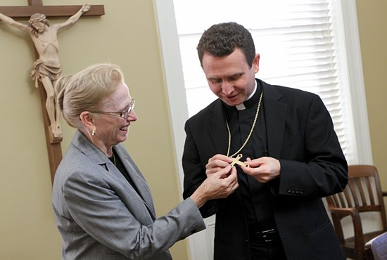 Bishop-elect Andrew Cozzens shows his mother, Judy, a pectoral cross given to him by Archbishop John Nienstedt. (Dave Hrbacek/The Catholic Spirit)