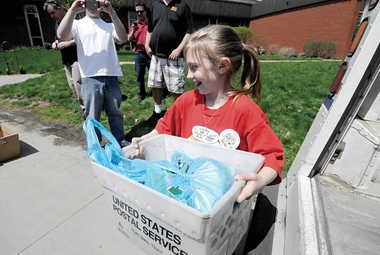 Alexis Lamprecht helps unload one of six U.S. Postal Service trucks that delivered food from the Stamp  Out Hunger Food Drive to Presentation of the Blessed Virgin Mary School, in Maplewood May 10.  Dianne Towalski/The Catholic Spirit