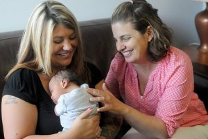 Kristin Wermus, right, a master-certified life coach and client services director, visits with Aleesha Warner and her 2-week-old son Jayden at Pregnancy Choices in Apple Valley in this 2014 file photo. Dianne Towalski / The Catholic Spirit.