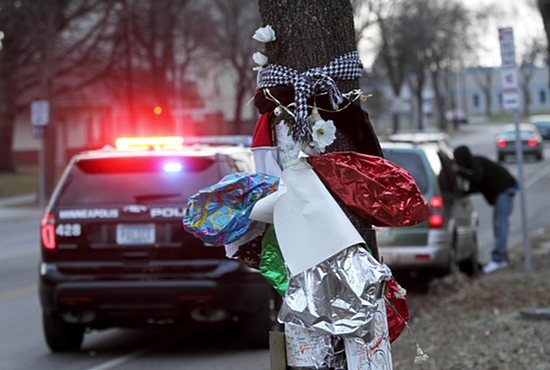 Balloons, flowers and signs mark the site where Jamar Clark was shot by a police officer Nov. 15 in north Minneapolis. Clark died the following day. Dave Hrbacek/The Catholic Spirit