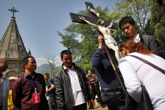 A Chinese Catholic kisses a crucifix during a pilgrimage in Baoji, China, in this May 3, 2013, file photo. Chinese authorities are continuing their campaign of removing crosses in Zhejiang province, and one of the latest was taken from a Catholic Church. CNS photo/Wu Hong, EPA