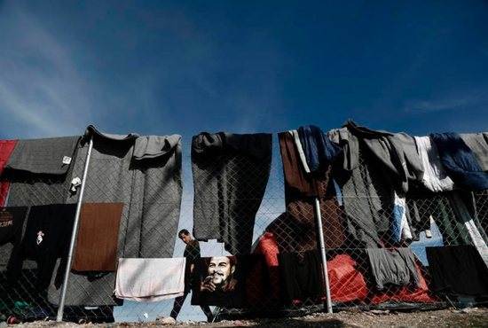 A refugee walks by clothes drying on a fence at a refugee camp in Idomeni, Greece, March 8. CNS photo/Yannis Kolesidis, EPA
