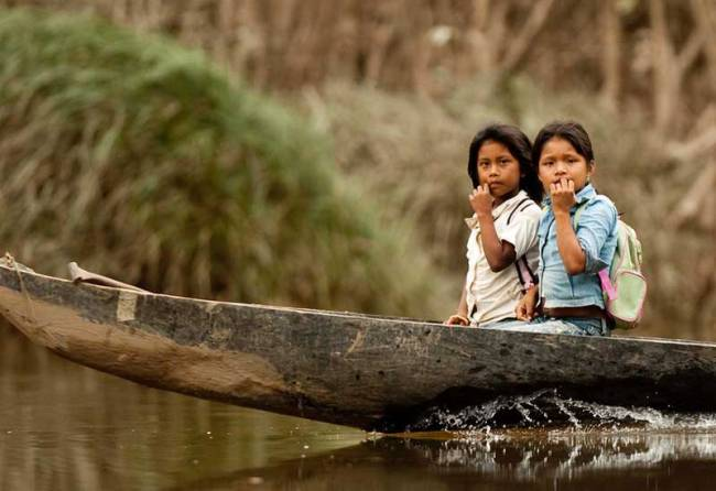 Children head to school in their dugout in the Amazon.