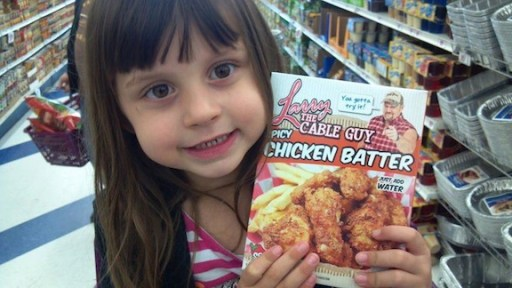 A girl poses with a package of Larry the Cable Guy Chicken Batter.
