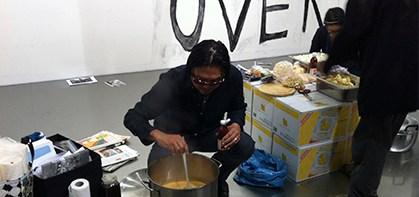 Rikrit Tiravanija sirviendo comida en la inauguración de Criticism en la Gund Gallery, 2015