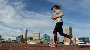 A runner makes her way through the Baltimore Inner Harbor on an autumn day.  (The Daily Record/Maximilian Franz)