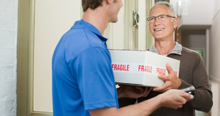 Smiling older man receives box delivered to his door
