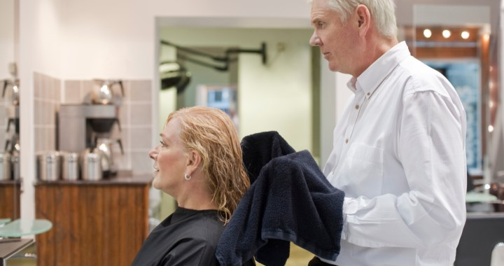 Mature woman getting hair shampooed and cut by male hair stylist