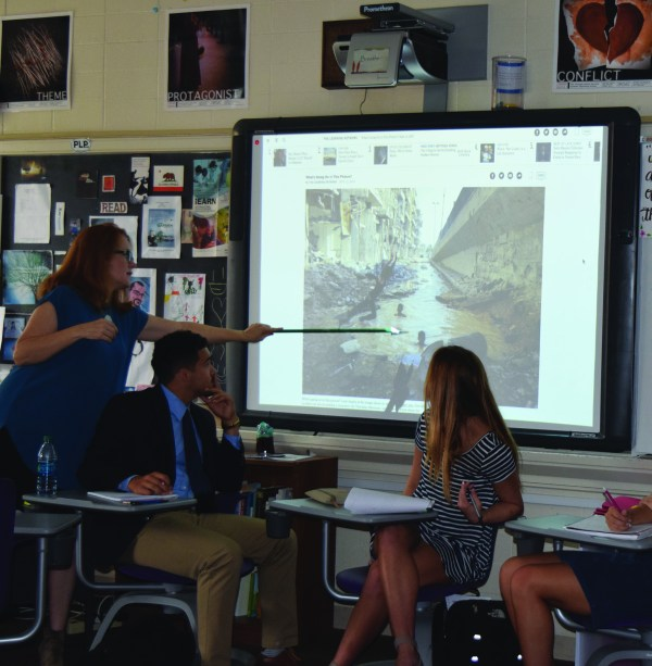 Ms. Forster points to the photo displayed on the board, to help her students analyze the context of the photo. Photo by Marley Orange.