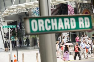 Pedestrians and shoppers cross Orchard Road shopping strip in Singapore