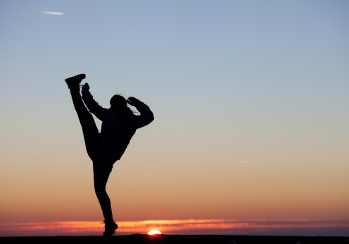 woman kicking sunset
