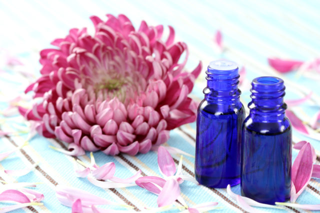 essential oils and flower on the green divas