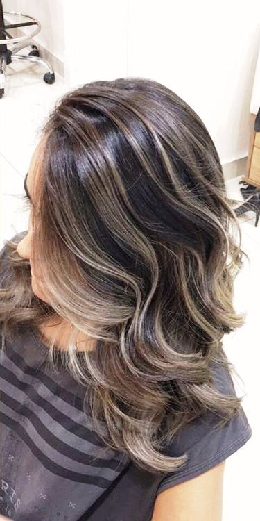 The faded blonde highlights on the dark cold-toned hair