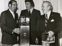 Alan Eagleson (left) Phil Esposito (middle) and Lester B. Pearson (right) standing behind a table with two Lester B. Pearson awards on the table. [photo: Canada's Sports Hall of Fame]