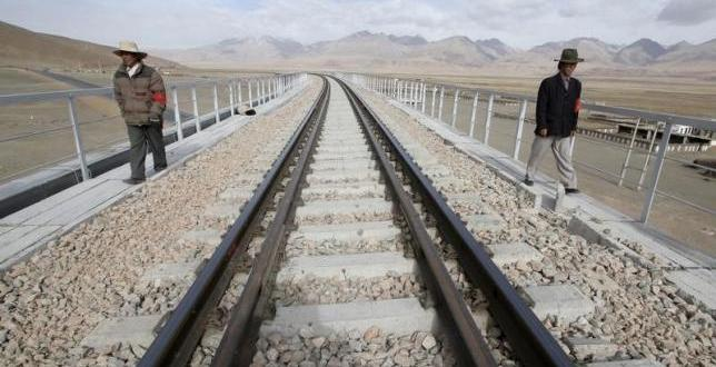 Two workers walk along the Qinghai-Tibet Railway as they check the railway track in Dangxiong county of the Tibet Autonomous Region, April 20, 2007. REUTERS/Simon Zo/Files