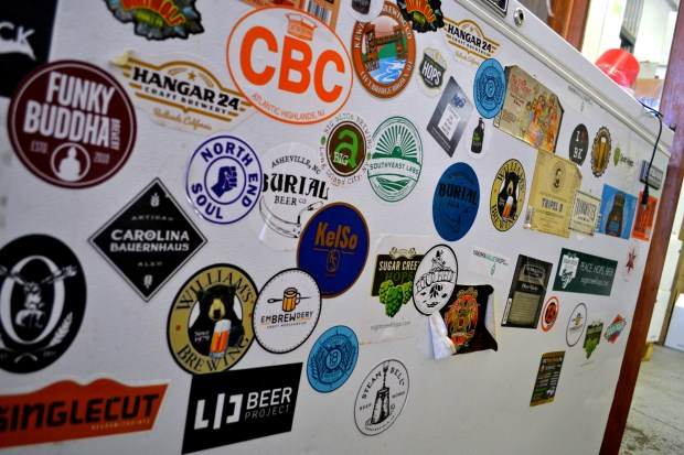 Stickers from craft breweries, including one from LIC Beer Project, on a fridge at Transmitter Brewery. Four breweries opened in Long Island City alone in the last three years. (Ariana Igneri / The Ink)