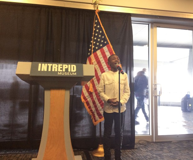 Miles Caton sang the Star-Spangled to begin the Pearl Harbor commemoration ceremony aboard the USS Intrepid. (The Ink/Katryna Perera)