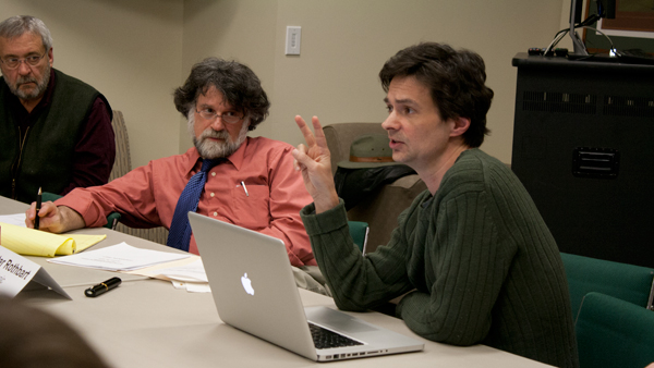 From left, Peter Rothbart, professor of music theory, history and composition, listen as Steven Skopik, chair of media, arts sciences and studies and representative of the Faculty Handbook Amendment Committee, addresses the Faculty Council Tuesday in the VIP Room in the A&E Center.