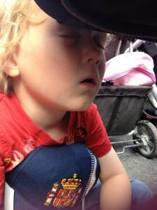 sleeping on the ground against the pram