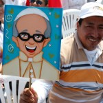 A man holds an image of Pope Francis as he waits for the start of the pope's Mass in Los Samanes Park in Guayaquil, Ecuador, July 6. (CNS photo/Paul Haring) See POPE-FAMILY July 6, 2015.