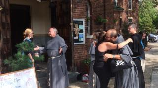 Conventual Franciscan friars greet the residents of the Greenpoint/Williamsburg section of Brooklyn, N.Y., Aug. 23, 2015, shortly after they opened their San Damiano Mission in the neighborhood, which had been the Holy Family (Slovak) Church. (CNS photo/Ed Wilkinson) See MISSION-HIPSTERS Aug. 24, 2016.