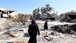 People walk amid rubble Sept. 19 in the city of Homs, Syria. (CNS photo/Mohammed Badra, EPA) See CHALDEAN-BISHOPS-SYNOD and POPE-SYRIA-IRAQ-AID Sept. 29, 2016.