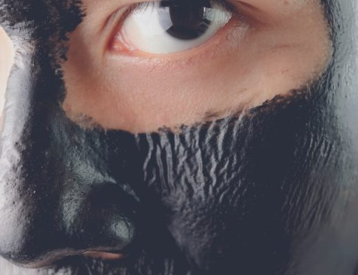 Man treating his facial skin with an activated charcoal mask