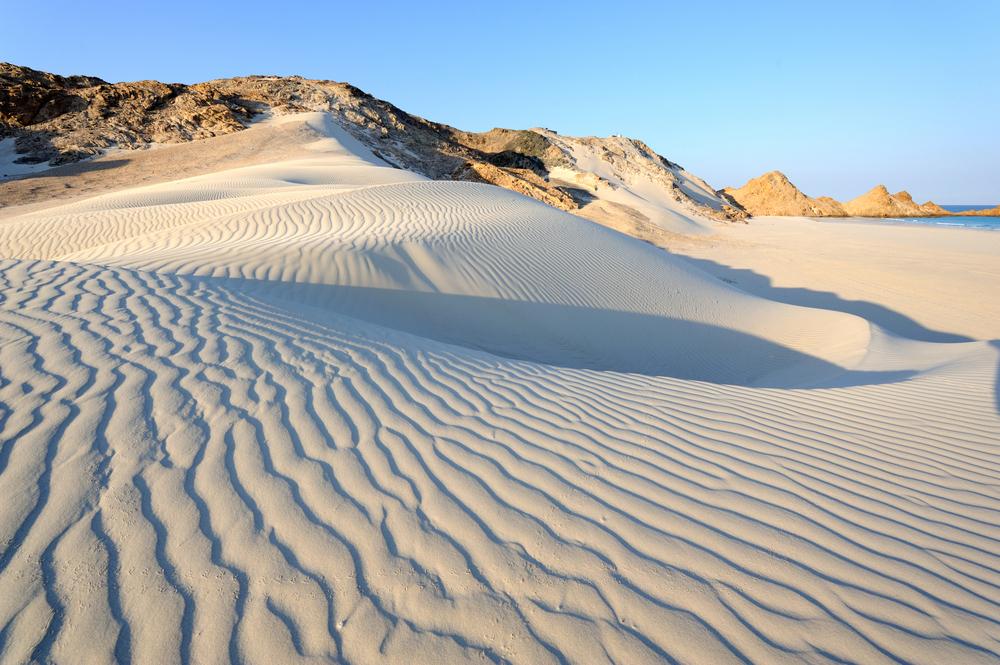 Sand dunes touching rocky cliffs