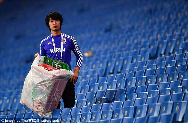 Japanese fan in tears cleaning up the stands after the match