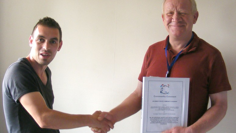 Cpl Garry Langridge (right) shakes hands with Dave Cash, Center Manager of The Hub at The HILT Foundation, after receiving the keys to his new accommodation achieved with help from the Lincolnshire Armed Forces Community Covenant